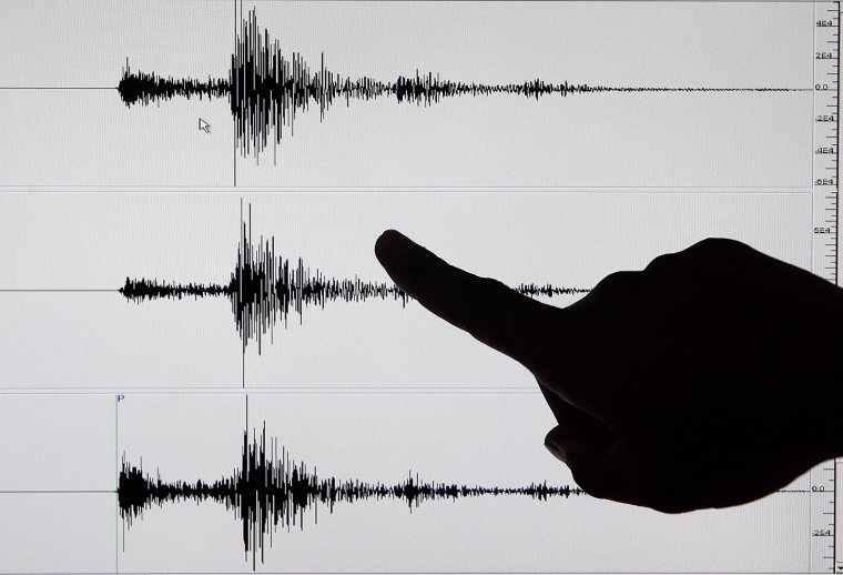 A Filipino Senior Science Research Specialist points to recorded tremors on a seismogram
